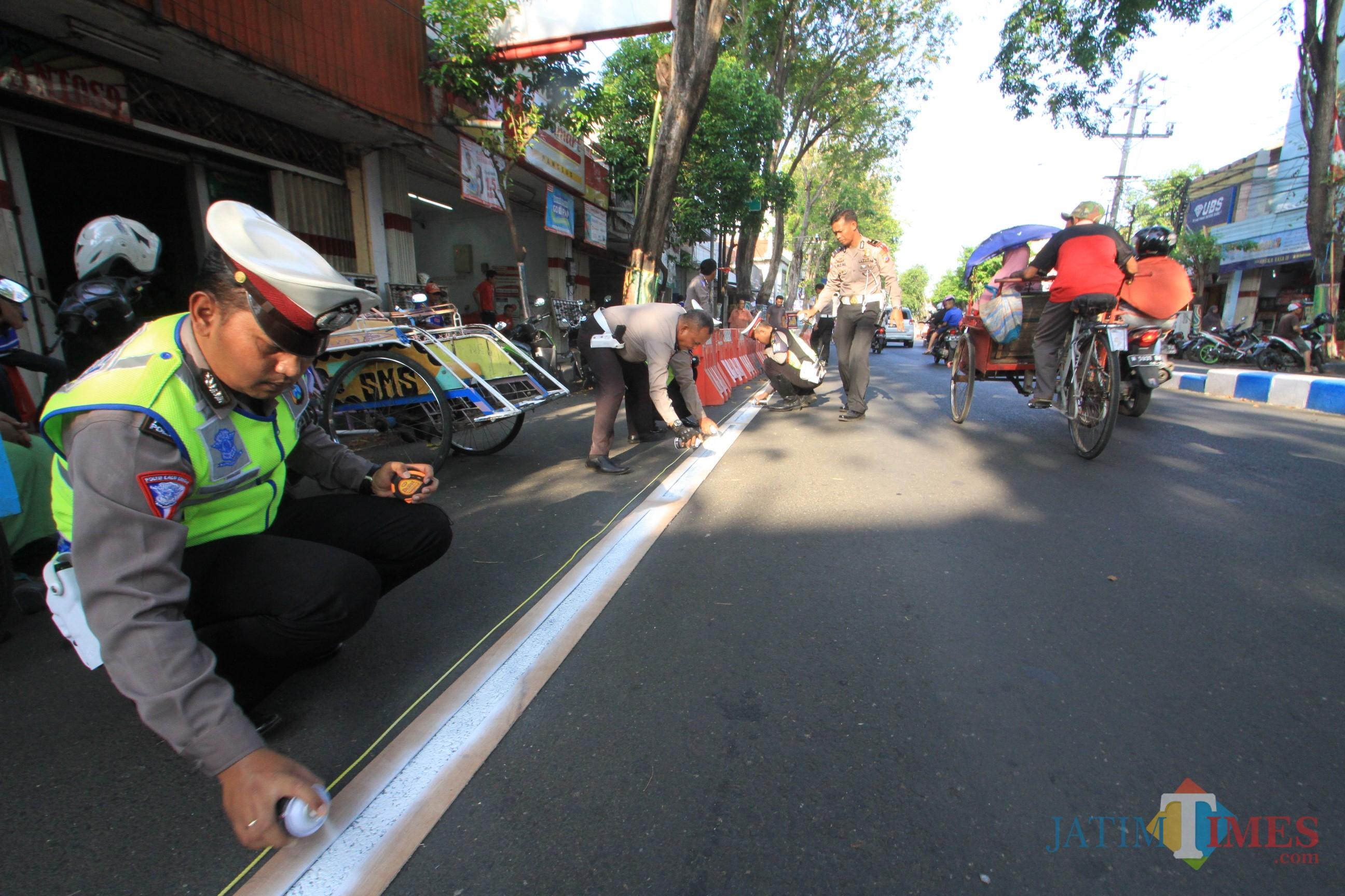 Petugas Satlantas tengah mengecat pembatas parkir (Agus Salam/Jatim TIMES)
