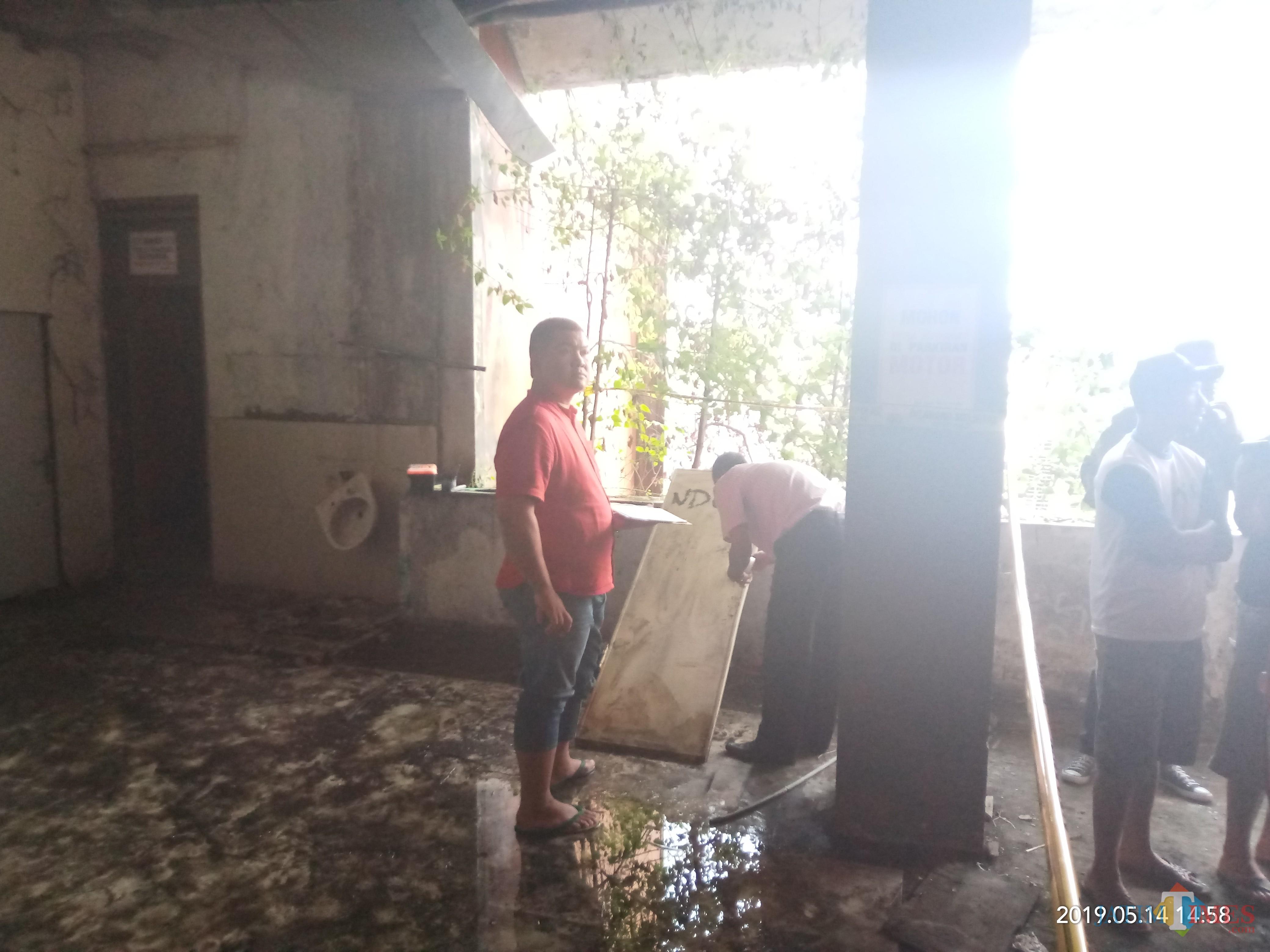Polisi yang tengah memeriksa sidik jari pada bagaian pintu kamar mandi (Anggara Sudiongko/MalangTIMES)