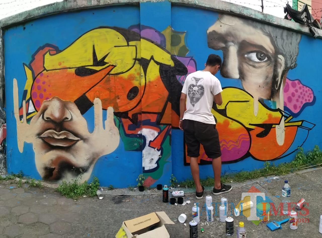 Salah satu seniman grafiti menuangkan idenya ke dalam sebuah lukisan tembok. (eko Arif s /JatimTimes)