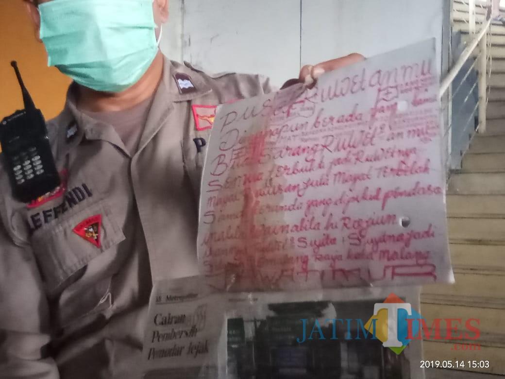 Polisi saat menunjukkan tulisan tangan yang diduga ditulis oleh pelaku mutilasi perempuan di Malang. (Foto: Dokumen MalangTIMES)