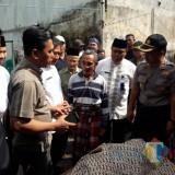 Petugas Polsek Genteng bersama warga  membawa jenazah korban ke rumah kerabatnya