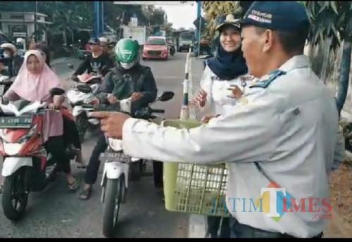 Petugas UPT Dishub Dampit saat membagikan takjil kepada masyarakat (Nana)
