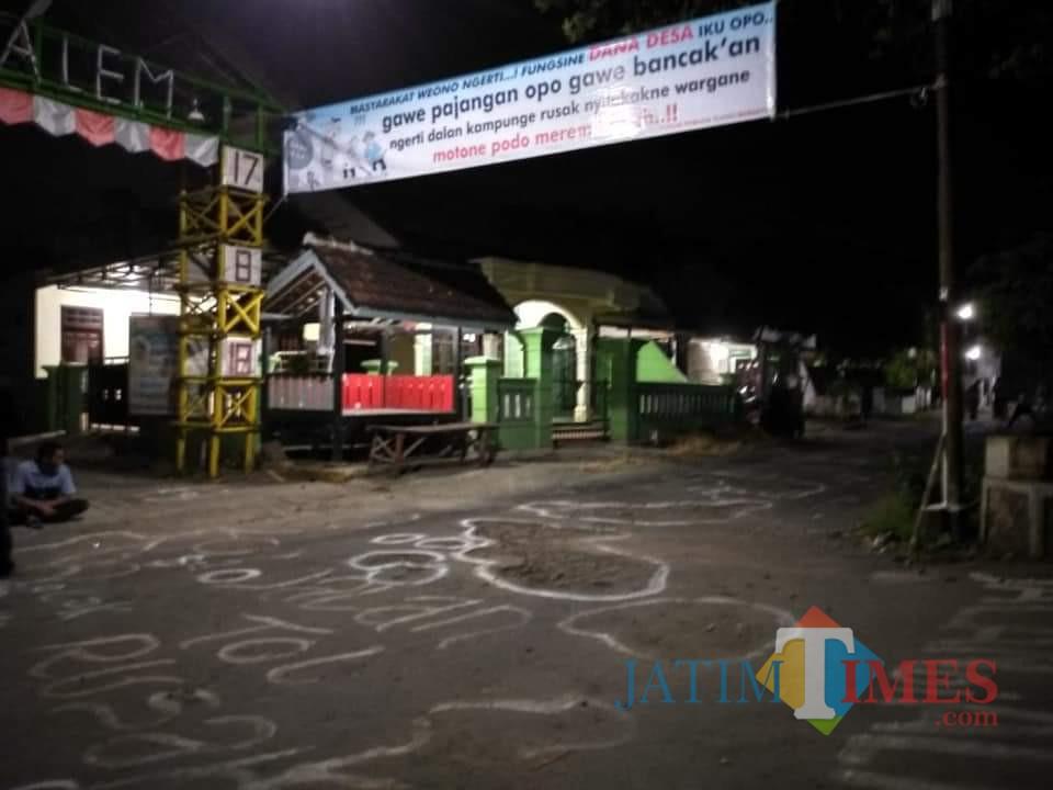 Warga mencorat coret dan memasang spanduk di jalan Desa Tlogo yang rusak
