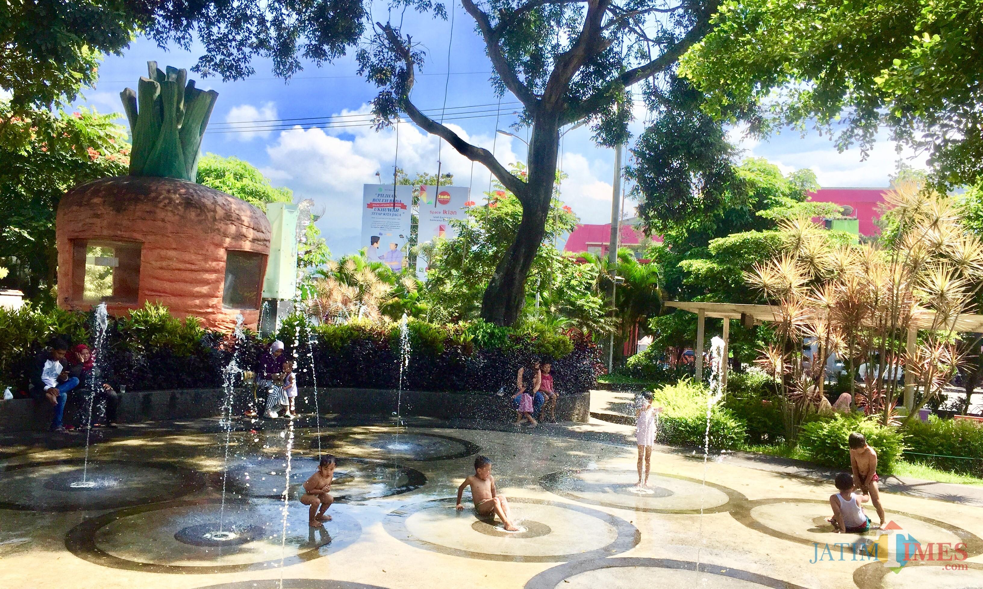 Beberapa anak-anak sedang asyik menikmati air mancur di Alun-Alun Kota Batu. (Foto: Irsya Richa/MalangTIMES)