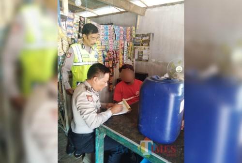 Riadi (baju merah), penjual miras, saat ditindak oleh petugas kepolisian di  Kecamatan Pagelaran. (Foto : Humas Polres Malang for MalangTIMES)