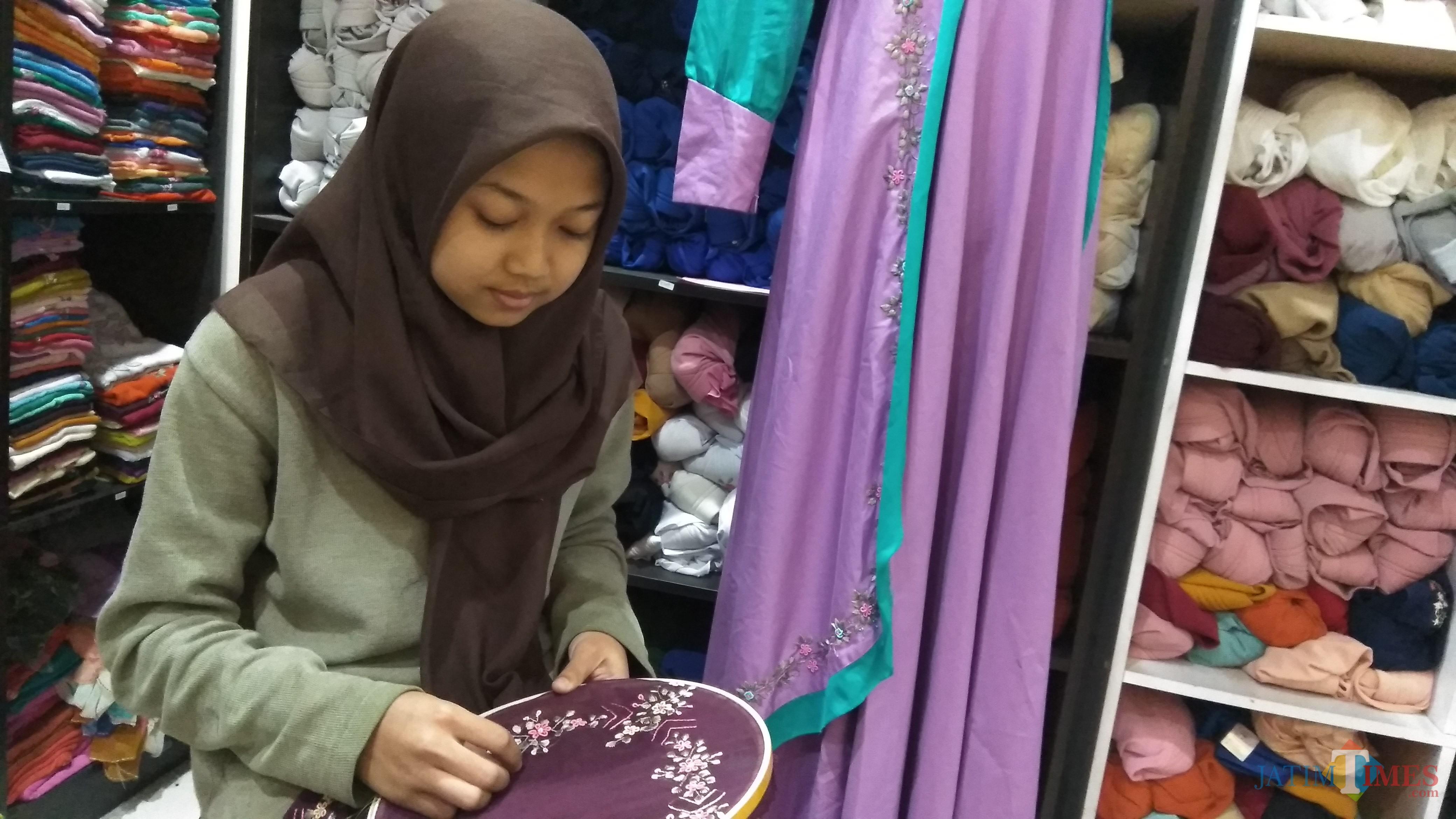 Perajin tengah menyulam hiasan di kerudung di rumah fashion Almira Handmade, Kota Malang. (Foto: Nurlayla Ratri/MalangTIMES)