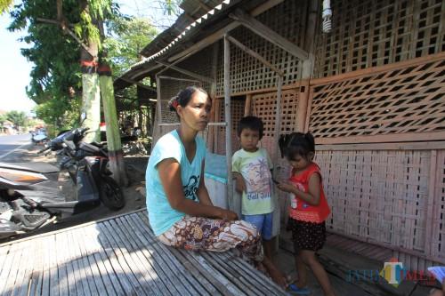 Supriya, istri penemu Hp yang ditahan  bersama 2 anaknya berlatar belakang rumahnya (Agus Salam/Jatim TIMES)