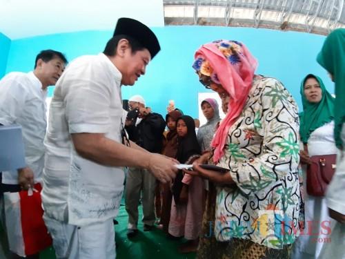 Komisaris PT ACA Iwan Kurniawan (kopyah Hitam) memberikan santunan kepada duafa di Balai Desa Pagak, Kabupaten Malang. (Foto:Hezza Sukmasita/MalangTIMES)