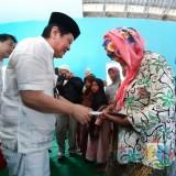 Komisaris PT ACA Iwan Kurniawan (kopyah putih) memberikan santunan kepada duafa di Balai Desa Pagak, Kabupaten Malang. (Foto:Hezza Sukmasita/MalangTIMES)
