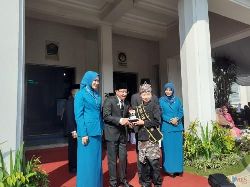 Wali Kota Malang Sutiaji saat menerima penyerahan penghargaan Raka Cilik Jawa Timur 2019 dari Gerald Ramadhan Yusuf. (Arifina Cahyanti Firdausi/MalangTIMES)