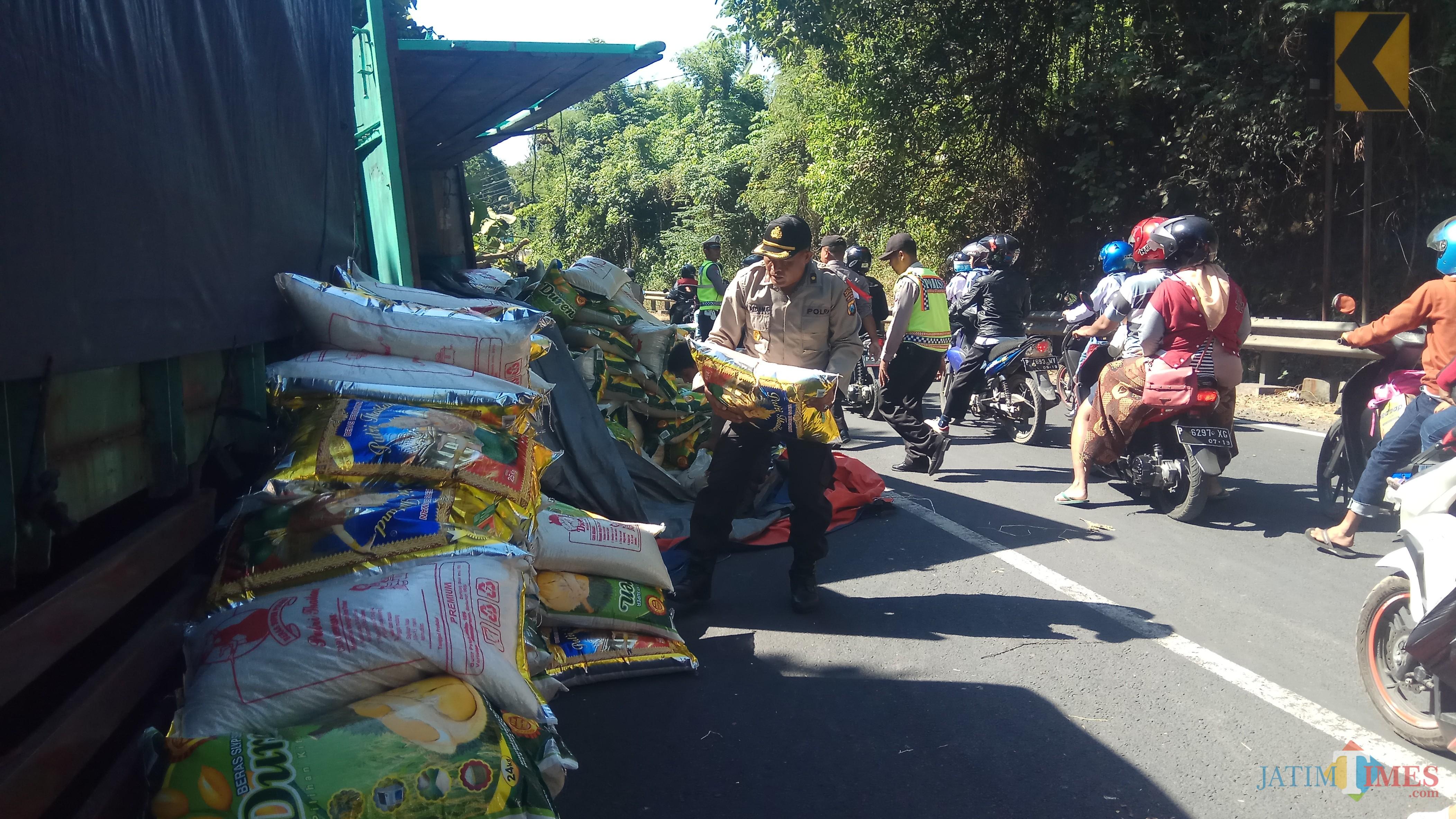 Petugas kepolisian memindahkan beras yang berada di badan jalan.