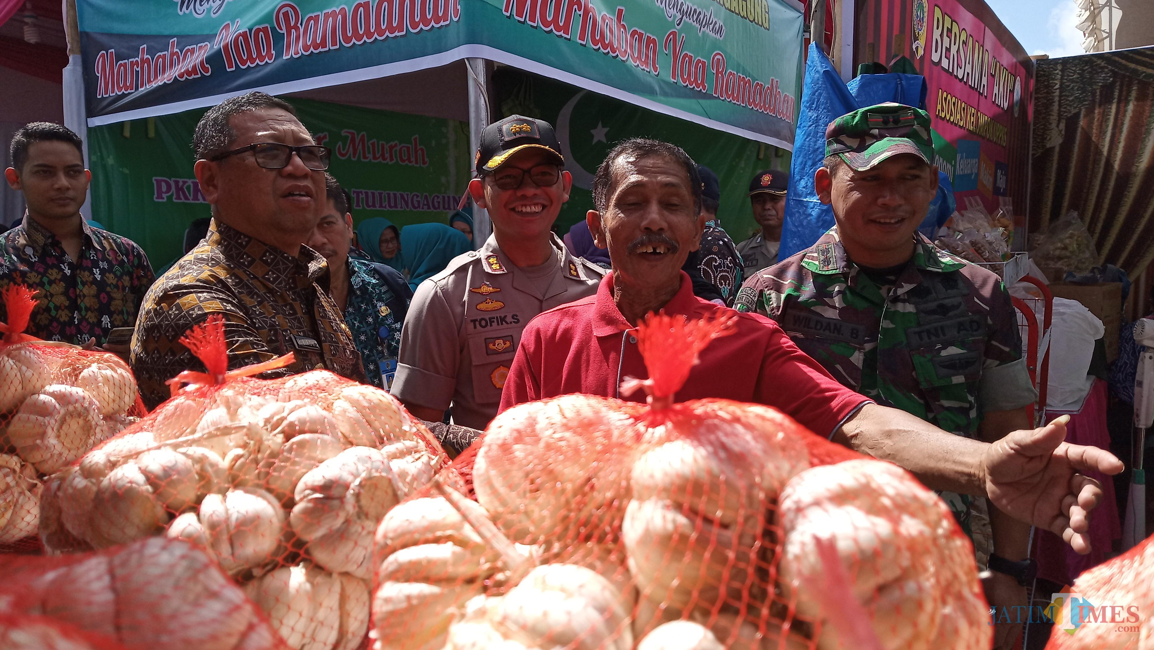 Plt Bupati Tulungagung (kiri)  didampingi Kapolres dan Dandim melihat kondisi pasar murah (foto : Joko Pramono/Jatim Times)