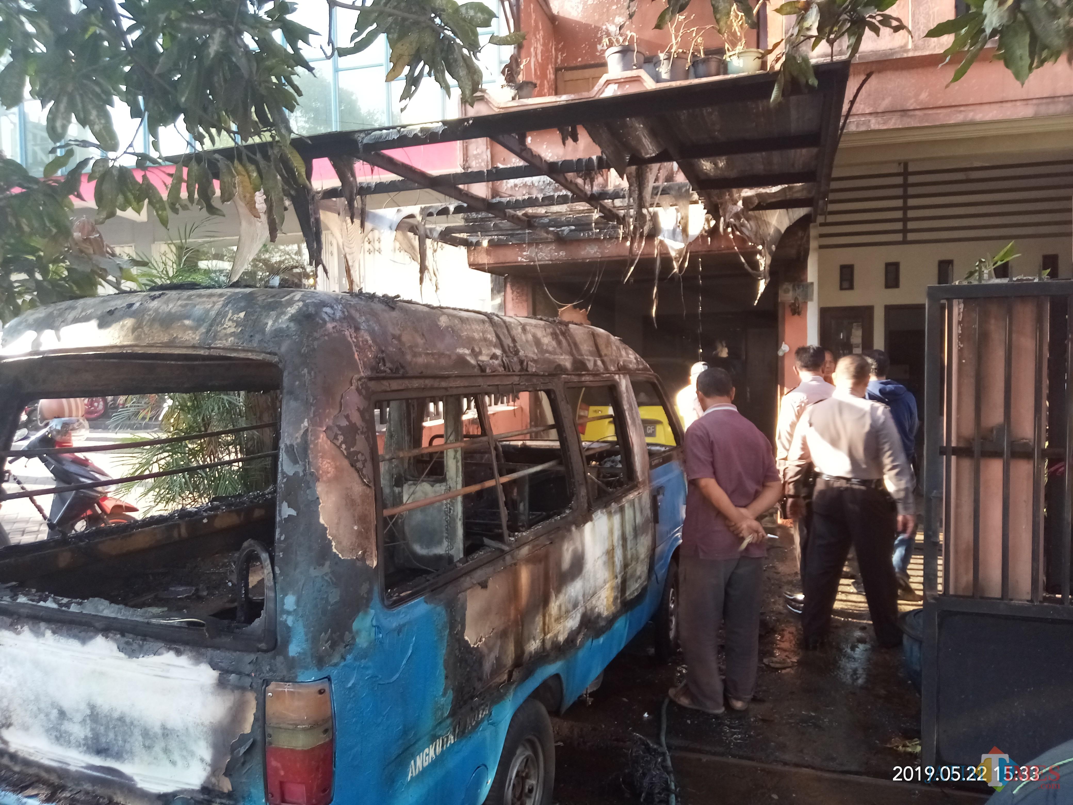 Angkot dan atap rumah yang terbakar habis sedang diperiksa pihak kepolisian (Anggara Sudiongko/MalangTIMES)