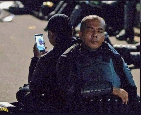 Foto dua aparat kepolisian di tengah demo 22 Mei yang viral di medsos.(Ist)