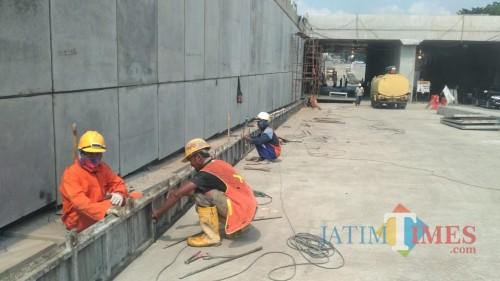 Pekerja tengah melakukan pemasangan beton di underpass Karanglo, Kabupaten Malang. (Foto: Nurlayla Ratri/MalangTIMES)