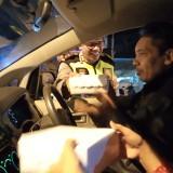 Kapolres Tulungagung, AKBP Tofik Sukendar saat menyerahkan nasi untuk sahur kepada pengendara. (foto :  joko pramono/jatimtimes)