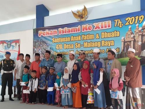 Komisaris Utama PT ACA Iwan Kurniawan (6 dari kiri, memakai kacamata hitam) saat memberikan santunan di Kecamatan Wagir. (Arifina Cahyanti Firdausi/MalangTIMES)