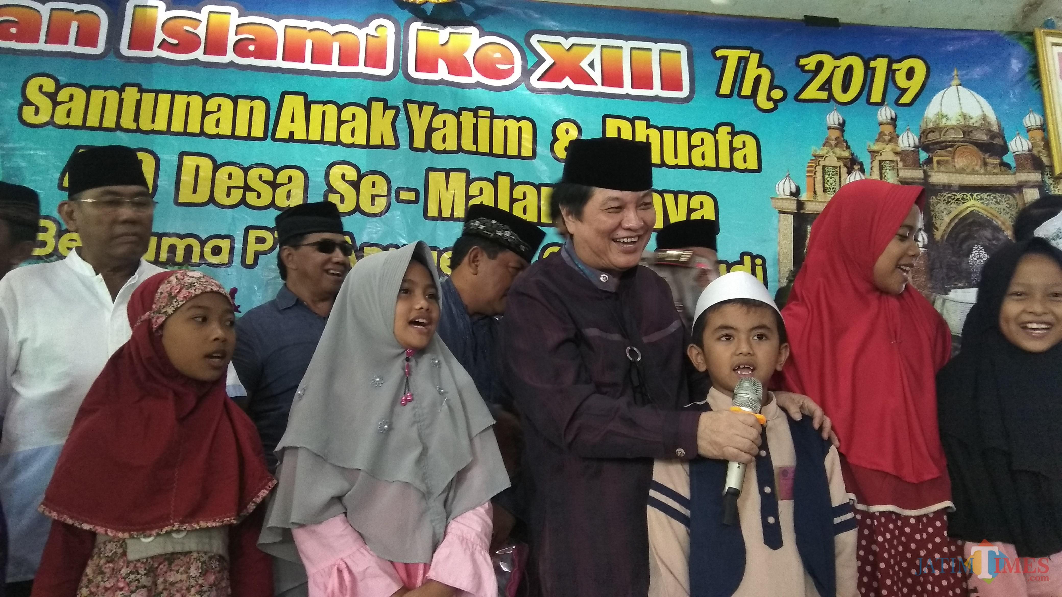 Komisaris Utama PT ACA Iwan Kurniawan (tengah) saat berbincang dengan anak-anak yatim di Kecamatan Bantur, Kabupaten Malang. (Foto: Nurlayla Ratri/MalangTIMES)