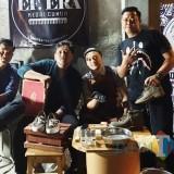 Aderay Putra Perdana (kanan) saat  membersihkan sepatu milik customer. (eko Arif s /JatimTimes)