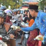Ketua Komunitas Honda Clasic Bagus Romadon saat membagikan takjil di perempatan Paron Kabupaten Kediri. (eko Arif s jatimTIMES)