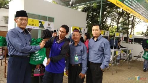 Kepala Baznas Kota Malang Sapardi menyerahkan paket santunan secara simbolis pada tenaga honorer. (Foto: Nurlayla Ratri/MalangTIMES)
