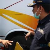 Sejumlah petugas Dishub saat mengecek kondisi ban bus yang ditemukan dalam kodisi gunduk atau tidak layak pakai. (Foto : Adi Rosul / JombangTIMES)