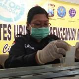 Petugas BNN Kota Kediri memeriksa air seni salah sopir bus. (eko Arif s /JatimTimes)