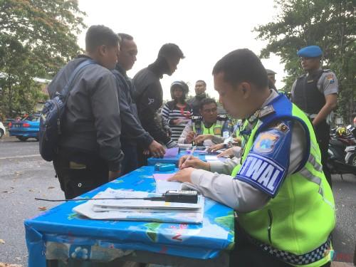 Petugas kepolisian saat memberikan surat tilang kepada pengguna jalan karena tidak memiliki SIM. (Foto : Ashaq Lupito / MalangTIMES)