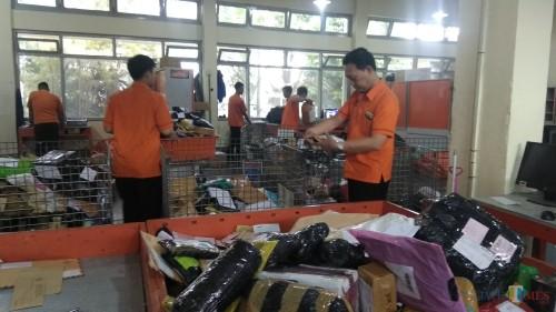 Para petugas Kantor Pos Malang tengah melakukan penyortiran barang kiriman. (Foto: Nurlayla Ratri/MalangTIMES)