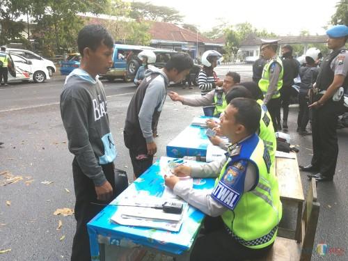 Petugas kepolisian saat menilang ribuan pengguna jalan karena tidak mengenakan helm di Kabupaten Malang. (Foto : Ashaq Lupito / MalangTIMES)