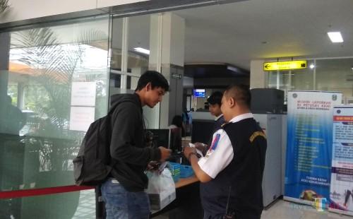 Petugas Bandara Abd Saleh Malang saat membantu penumpang di terminal keberangkatan. (Foto: Nurlayla Ratri/MalangTIMES)