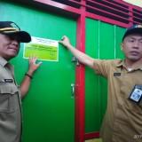 Kepala Disdag Kota Malang, Wahyu Setianto (Kiri) saat melakukan warning dengan penempelan stiker di kios pedagang yang menunggak( Anggara Sudiongko/MalangTIMES)