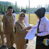 Bupati Jombang Hj Mundjidah Wahab menyerahkan SK CPNS seusai gelar apel dan halal bihalal di lapangan pemkab Jombang. (Foto : Adi Rosul / JombangTIMES)