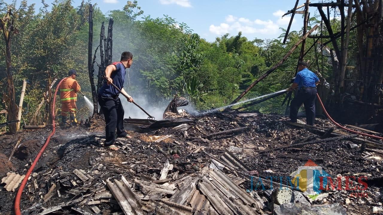 Petugas Damkar saat melakukan pembasahan rumah Samsul Hadi yang telah habis dilalap api (foto : Joko Pramono/JatimTIMES)