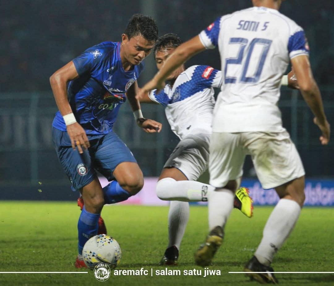 Dedik Setiawan (biru) saat diapit pemain lawan (official Arema FC)