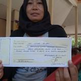 Warga tunjukan kuitansi pengurusan akta tanah.(foto : Joko Pramono/Jatim Times)