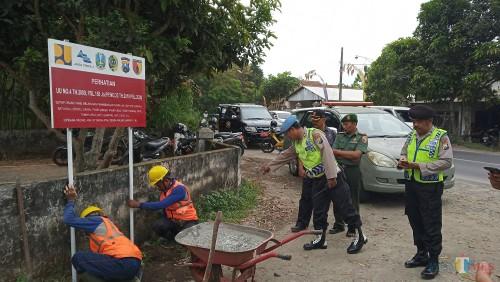Disaksikan TNI-Polri,  dan Satpol PP PJT memasang papan larangan penambangan pasir ilegal di tepi Kali Brantas (foto : Joko Pramono/Jatim Times)
