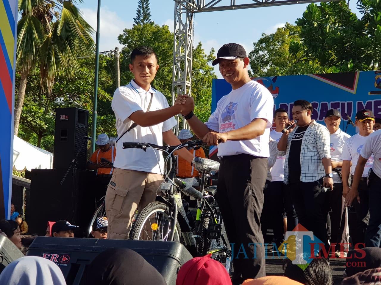 AKBP Tofik Sukendar Kapolres Tulungagung saat memberikan hadiah sepeda pada peserta senam bersama di Alun-Alun Tulungagung/ Foto : Dokpol / Tulungagung TIMES