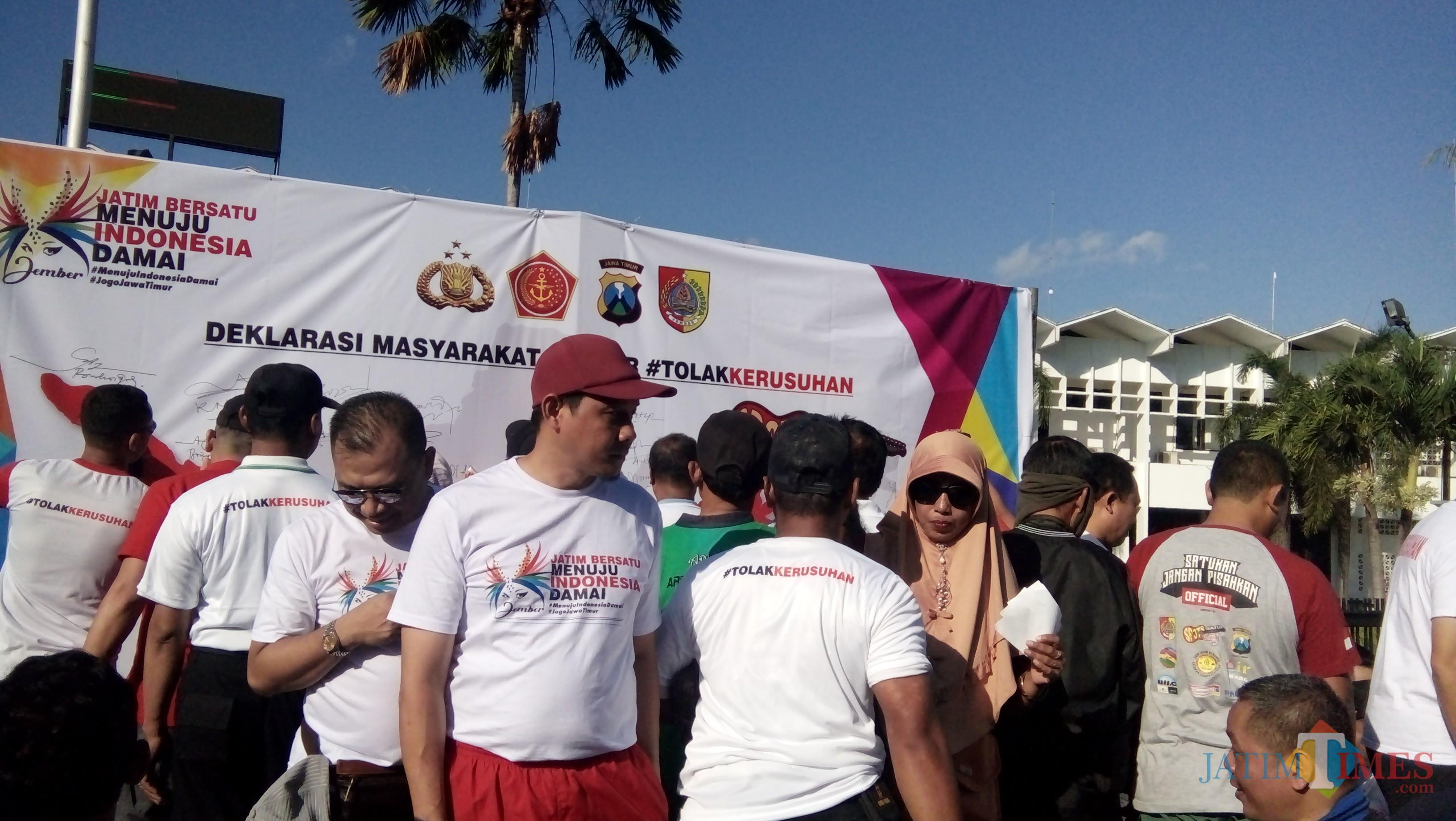 Beberapa warga saat bergantian membubuhkan tanda tangan di banner deklarasi masyarakat Jember tolak kerusuhan. (foto : Moh. Ali Makrus / Jatim TIMES)