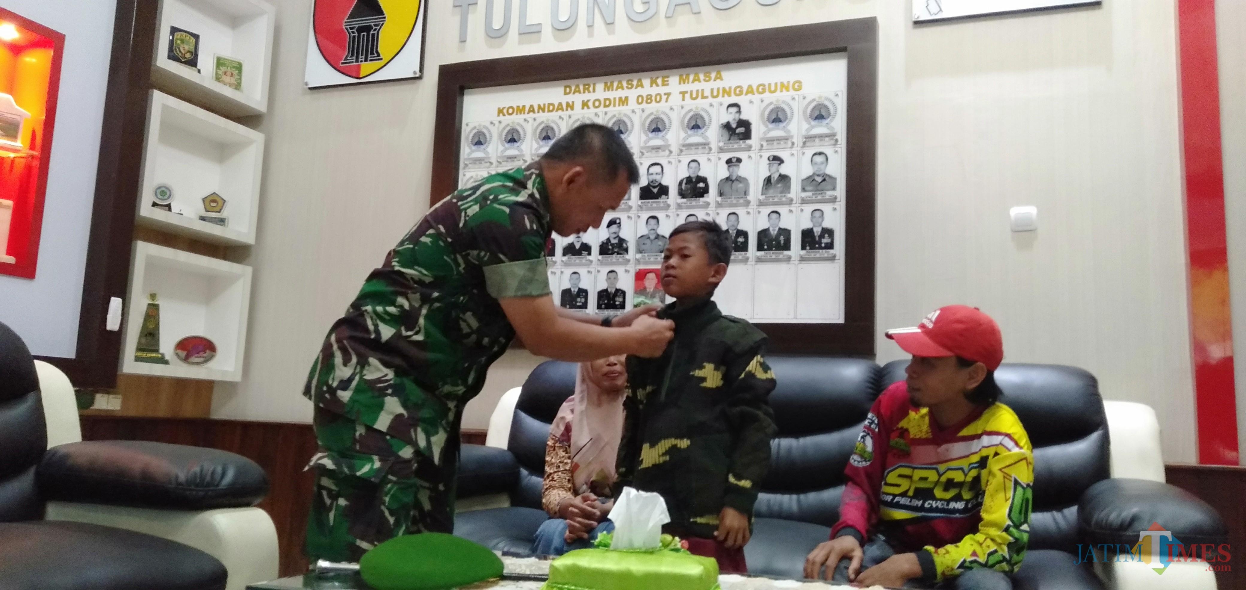 Komandan Kodim Tulungagung,  Letkol Wildan Bahtiar saat memakaikan jaket doreng pada Soni (foto: Joko Pramono/JatimTIMES)