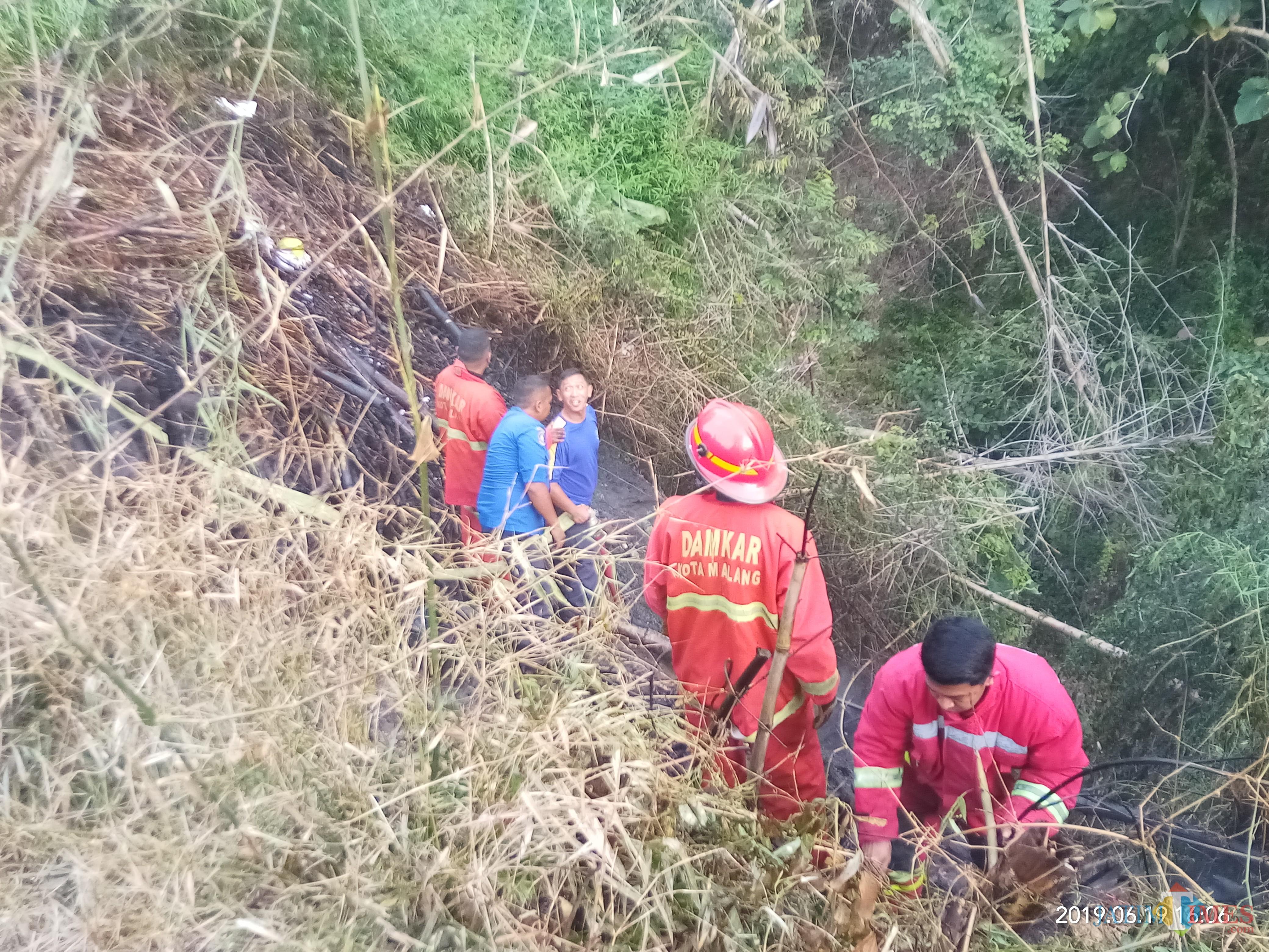Petugas PMK yang tengah berupaya memadamkan sisa bara api agar tidak kembali memicu kebakaran( Anggara Sudiongko/MalangTIMES)
