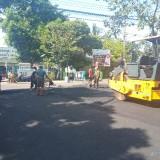 Petugas yang tengah melakukan pengaspalan dan pelebaran jalan. (Anggara Sudiongko/MalangTIMES)