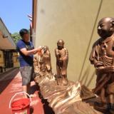 Salah satu jemaat membersihkan Dewa Arahat di Kelenteng Tri Dharma Sumber Naga Kota Probolinggo. (Agus Salam/Jatim TIMES)