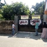 Senema (kiri berkaos putih) saat menunjukkan gerbang yang menuju akses rumahnya dalam kondisi terkunci (foto : Moh. Ali Makrus / JatimTIMES)