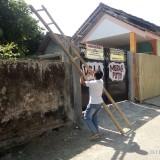 Senema saat mau masuk ke tempat tinggalnya harus menggunakan tangga untuk naik ke pagar tembok setinggi 2 meter (foto: Moh. Ali Makrus / JatimTIMES)