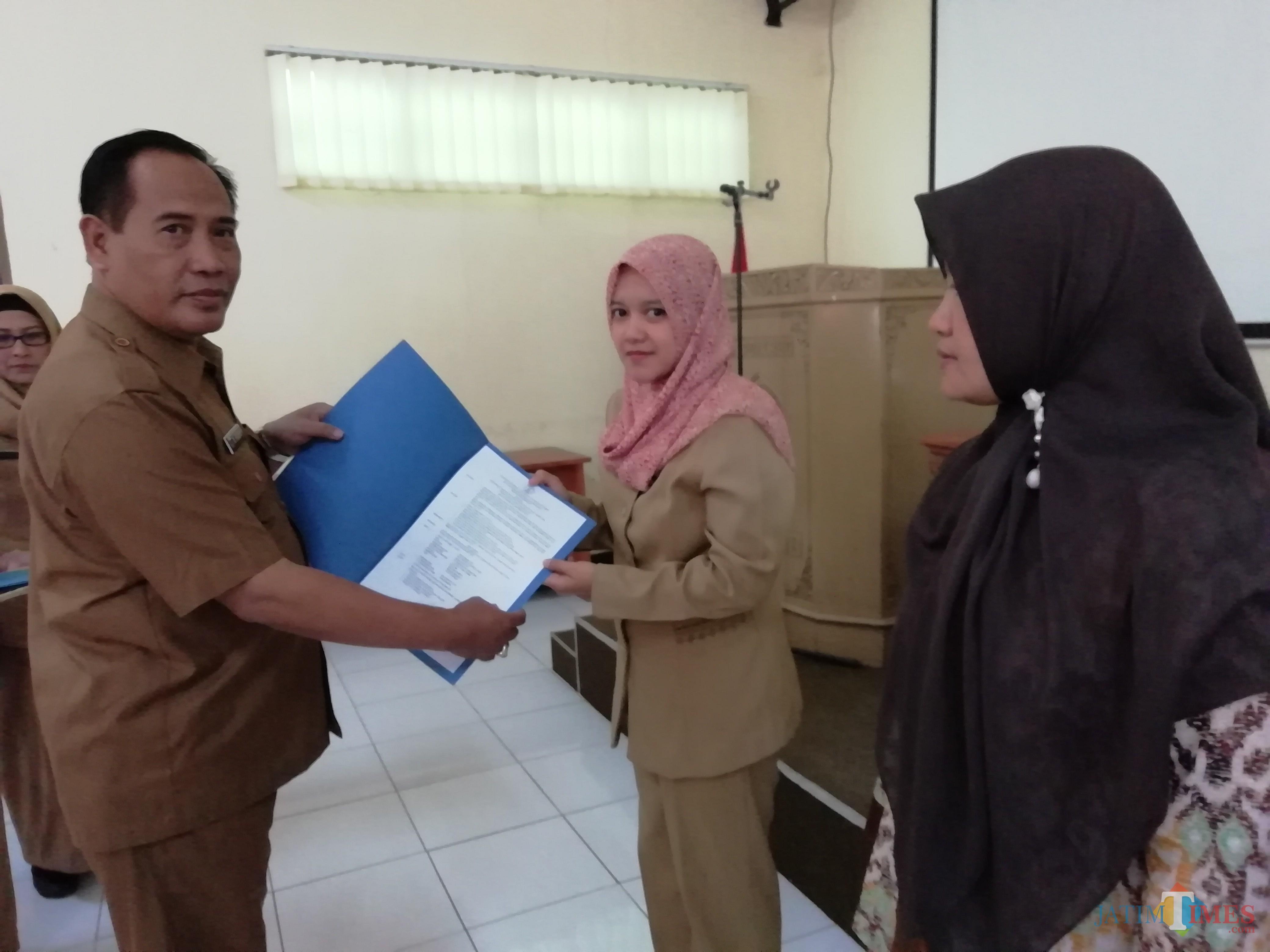 Kepala Dinas Pendidikan Kabupaten Malang M. Hidayat saat menyerahkan secara simbolis SK penyetaraan guru non-PNS, Selasa (25/06/2019). (Nana)