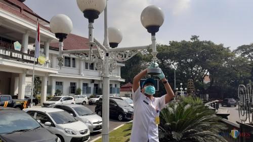 Petugas pengambil contoh DLH Kota Malang saat melepas alat Passive Sampler di kawasan Balai Kota Malang (Pipit Anggraeni/MalangTIMES).