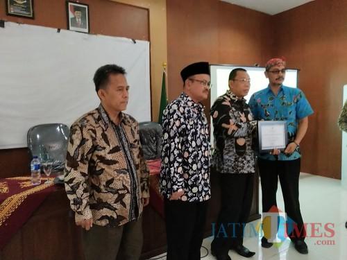Bupati Situbondo (baju batik cokelat) saat menyerahkan piagam ODF ke Kepala Desa Olean. (Foto Heru Hartanto / Situbondo TIMES)