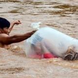 Seorang pria saat menyeberangkan anak dalam plastik di sebuah sungai. (Foto: istimewa)