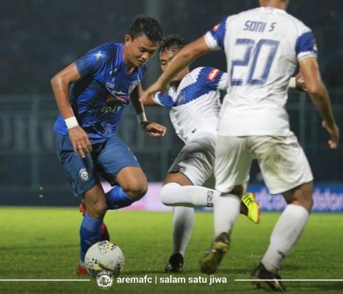 Dedik Setiawan (biru) saat diapit pemain lawan. (official Arema FC)